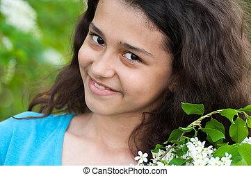 Teen girl with blooming bird cherry