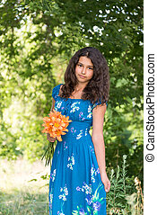 Teen girl with curly dark hair on nature - Teen girl with...
