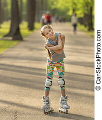 Teen girl with cute hairstyle skating in the park, hugging...