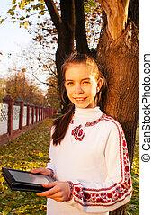 Teen girl with e-book reader in a park