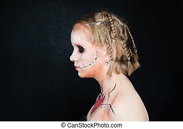 Teen Girl with Halloween Makeup. Profile on Blackboard Background