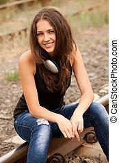 Teen girl with headphones at railways.