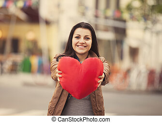 Teen girl with heart at outdoor.