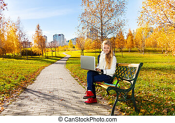 Teen girl with laptop in the park