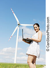 Teen girl with laptop next to wind turbine.