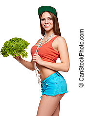 Teen girl with measurement tape holding lettuce