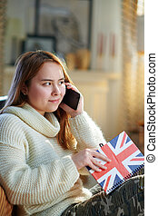 teen girl with notebook colors of British flag talking on phone