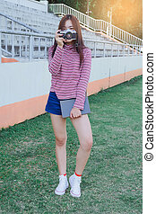 teen girl with old camera in hand .