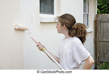 Teen Girl With Paint Roller - A teen girl rolling paint on...