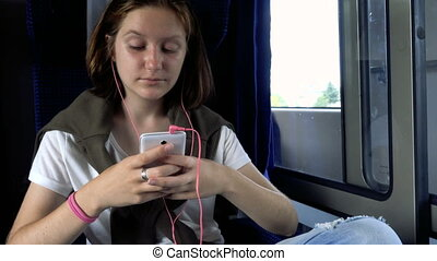 teen girl with the smartphone at the train