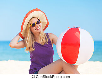 Teen girl with toy ball at the beach.