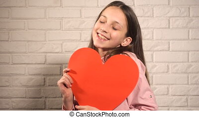 Teen girl withred big heart happy holding it and hugging