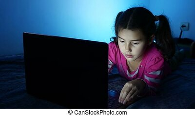 Teen girl working at a laptop, the Internet plays in the online entertainment game