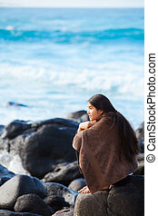 Teen girl wrapped in towel sitting on rocky beach