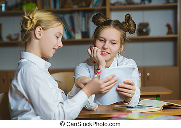 Teen girls in the school library or classroom, discussing what they are learning