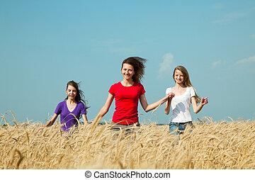 Teen girls running at the wheat field