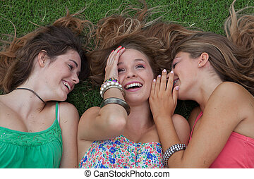 teen girls whispering and gossiping secrets