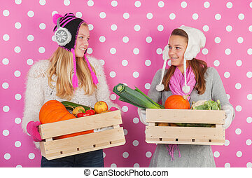 Teen girls with vegetables in winter