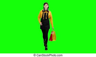 Teen goes with packages after shopping and looks around, today is a day of discounts. Green screen