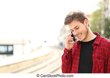 Teen guy calling on the mobile phone waiting a train -...