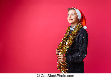 teen guy dressed in Santa hat and with tinsel around his neck making plans for the upcoming New year on red background