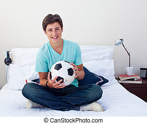 Teen guy holding a soccer ball in his bedroom