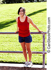 Teen Hispanic Woman Red Top Blue Shorts Outdoors