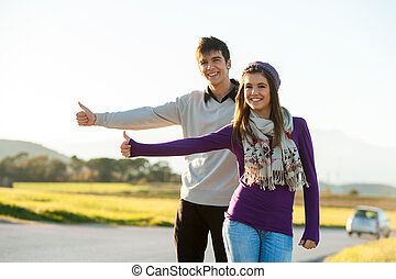 Teen hitchhikers along country road.