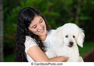 Teen holding a french poddle dog - Teen girl holding a white...