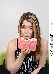 teen holding diary puzzled look
