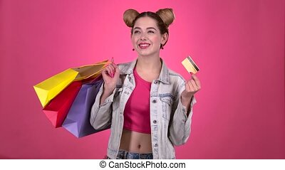 Teen holds shopping bags and a gold credit card. Pink...
