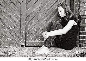 teen huddled in doorway