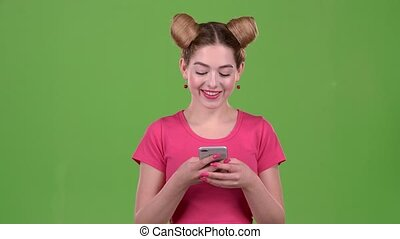 Teen in a pink topic prints a message on the phone. Green screen. Slow motion