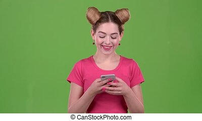 Teen in a pink topic prints a message on the phone. Green screen