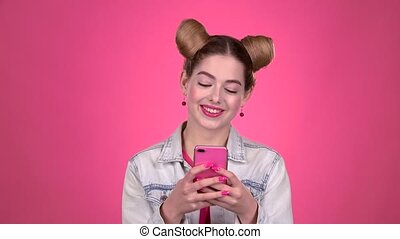 Teen in a pink topic prints a message on the phone. Pink background