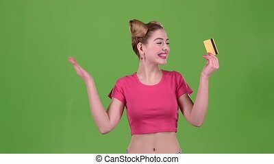 Teen in a pink topic with a credit card is happy. Green screen