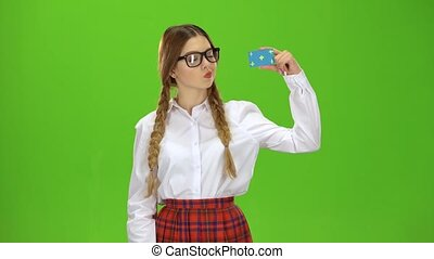 Teen in glasses raises a card and shows a ok . Green Screen