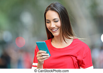 Teen in red using a blue smart phone on the street