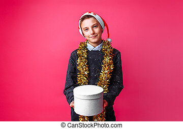 teen in Santa hat and tinsel on neck, got Christmas gift on red background. the concept of Christmas to give gifts