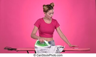 Teen ironing clothes with an iron on a pink board. Pink background