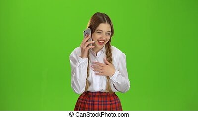 Teen is talking on the phone. Green screen