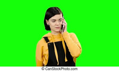 Teen is talking on the phone with his mom. Green screen