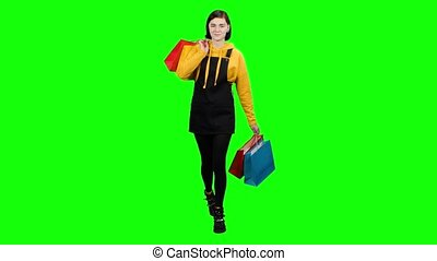 Teen is walking along the street with packages in her hands. Green screen