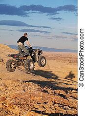 Teen jumping on quad ATV