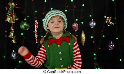 Teen kid girl in Christmas elf Santa Claus helper costume doing winner gesture, say Yes isolated on black background with garland. Child happily clenching fists. People New Year holidays celebration