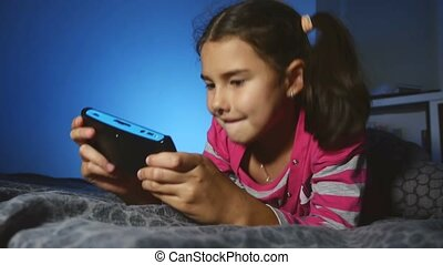 teen kid girl playing portable video online game a console...