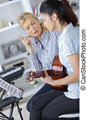 teen learning how to play the guitar with teacher