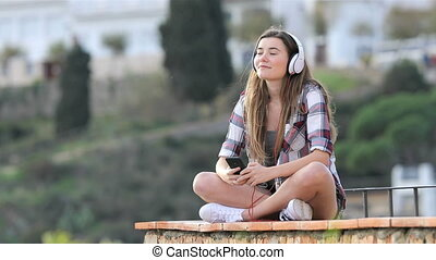 Teen listening to music and breathing on a ledge - Fullbody...