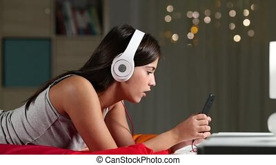 Teen listening to music and singing on a bed