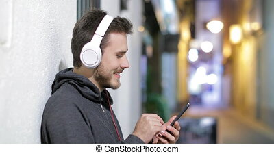 Teen listening to music in the night - Happy teenage boy...